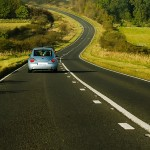 Car driving down a long road